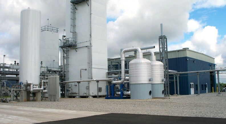 Molecular sieve unit and cold boxes near compressor building in New Carlisle, Indiana cryogenic air separation plant designed and supplied by UIG.