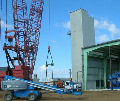 Liquefier (NLU) cold box about to be raised to vertical.  Note comprssor building on right and first two ASU cold box modules in place.