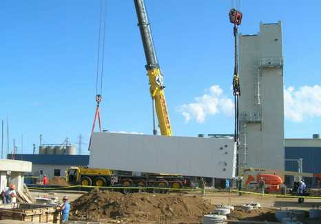 Liquefier (NLU) cold box being raised by lifting and tailing cranes.  Two ASU cold box modules and comressor building in right rear.